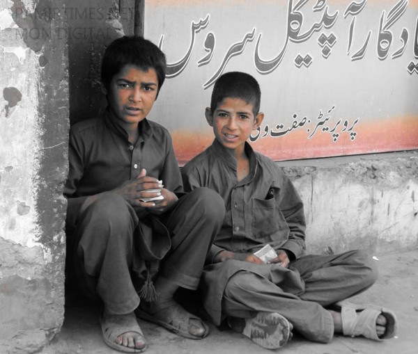 Two young kids counting money in the corner of a street in Gilgit. At this tender age the chances of young kids falling prey to social evils is very high.