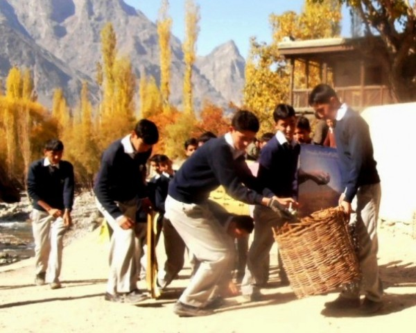 Students collect garbage from a street in the village in Shigar, Skardu (Baltistan)