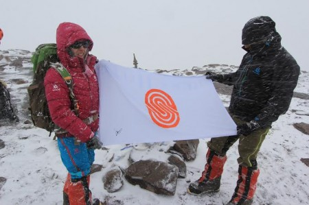 Samina and Mirza holding the flag of one of Serena Hotels, one of their sponsors