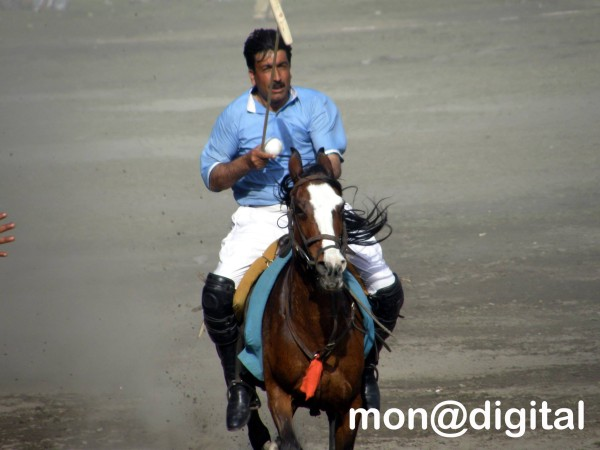 A polo player of team NLI prepares to hit the ball during a match in Gilgit