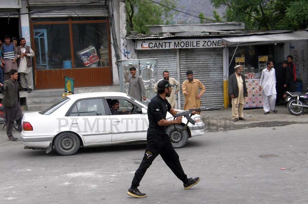 Gilgit: A police official aiming the gun at the unarmed protesters in Jutial area today
