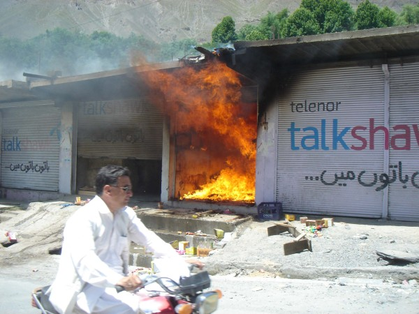 چترال، ایک شخص موٹر سائیکل پر جلتی ہوئی دکان کے سامنے سے گزر رہا ہے۔