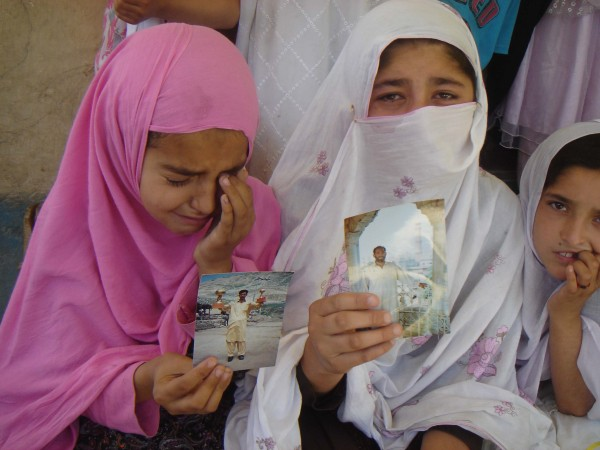 Children of the deceased holding the photographs of their dear ones