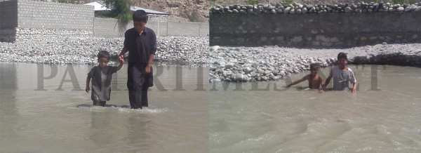 Locals crossing a flooded patch of land to reach their home in Musa Abad Colony in Jagir Baseen area of Gilgit. Photo: Farman Karim