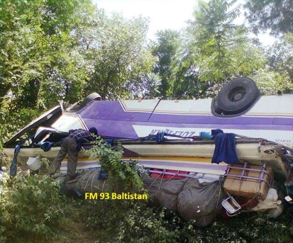 A local person looks inside the overturned bus in Mansehra