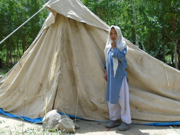 A student wearing her uniform stand outside a tent that is now her and her family's home
