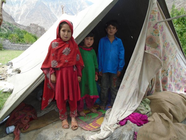 Children of a family that has been evacuated to a tent after the earthquake struck and damaged their house