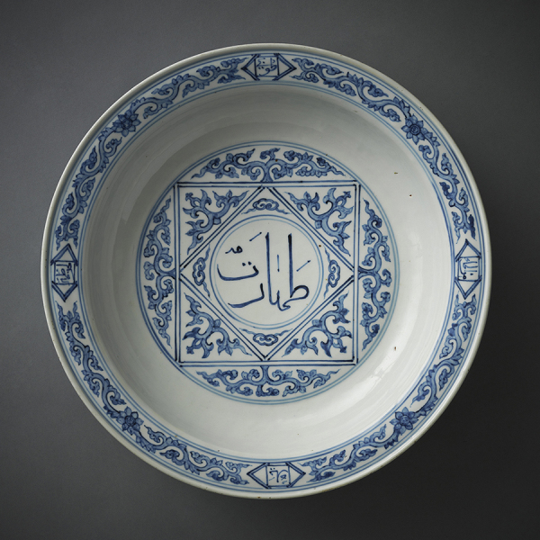 """Ablution basin: The multiple examples of sixteenth-century Chinese porcelain with Arabic inscriptions are testimony to the prominence at court of the Muslim community in China during that period, as well as the close and continuous contact between China and the Muslim world. This large dish was made in the porcelain kilns of the province of Jingdezhen in China for a Muslim patron, most probably a member of the close circle of Emperor Zhengde (reigned 1505–21) whose reign mark can be seen on the back of the dish. The word taharat (""""purity"""") is inscribed in Arabic in the central medallion of the dish, implying that it was meant for use in ablution, a basic requirement of Muslim prayer. The Chinese-style floral meander on the rim and its back frames several inscriptions that further evoke the concept of ritual purity and specifically mention ablution (al-wudu'). - Photo: AKDN"""