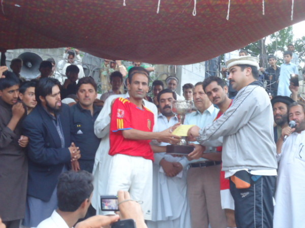 Captain of the winning team taking the trophy