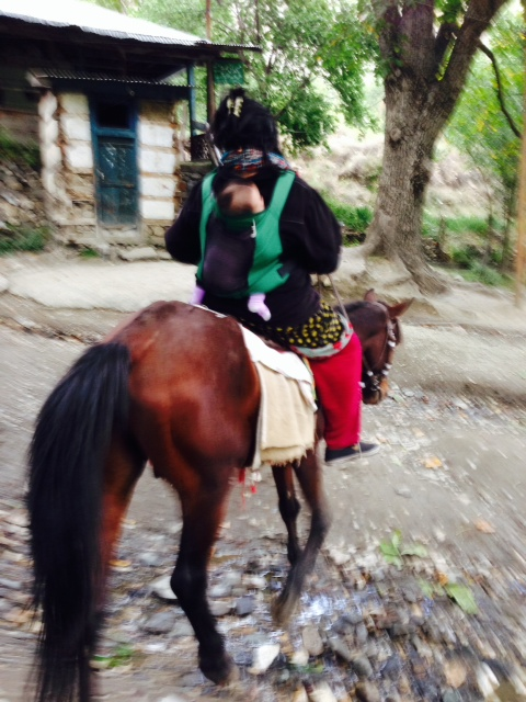 Travelling with baby on horseback ( introducing a new but safely-practiced tradition within local community). The writer later learned that it's a blunder and discourtesy to not cover the head esp. when being so bold; this was later redressed. Respectful dressing can give a traveler more access into the community's hearts and minds.