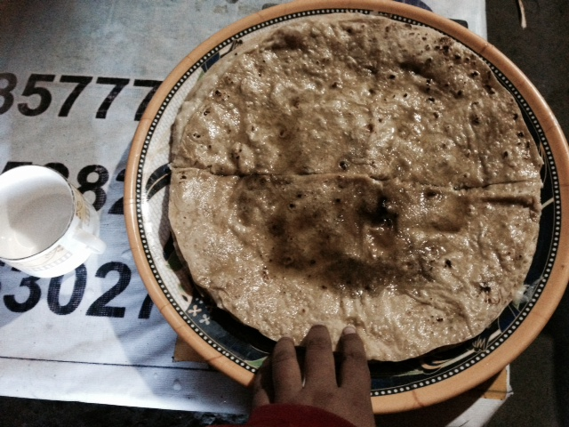 Eating local food (Shera Shapik—milk & wheat spread in flat-bread chapatis). A gift from the host community.