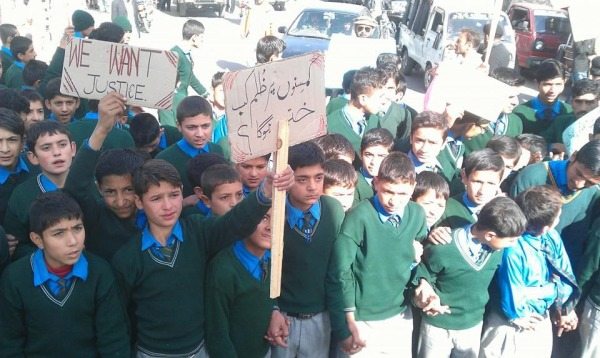 """""""When will the cruelty against children finish"""", reads the slogan on the placard held by this student"""