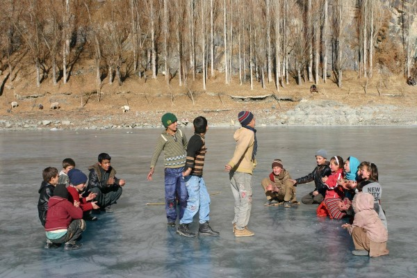 Children in large number run on the frozen surface, oblivious to the many risks involved
