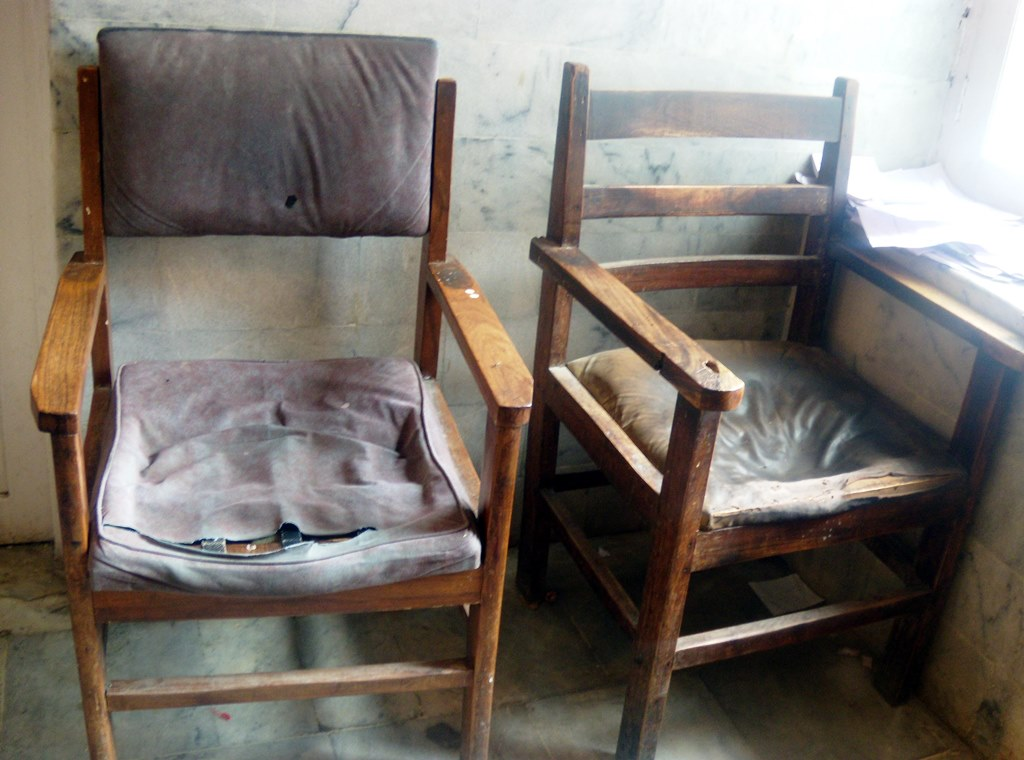 Two chairs for the hospital staff can be seen covered in dust and in shabby condition