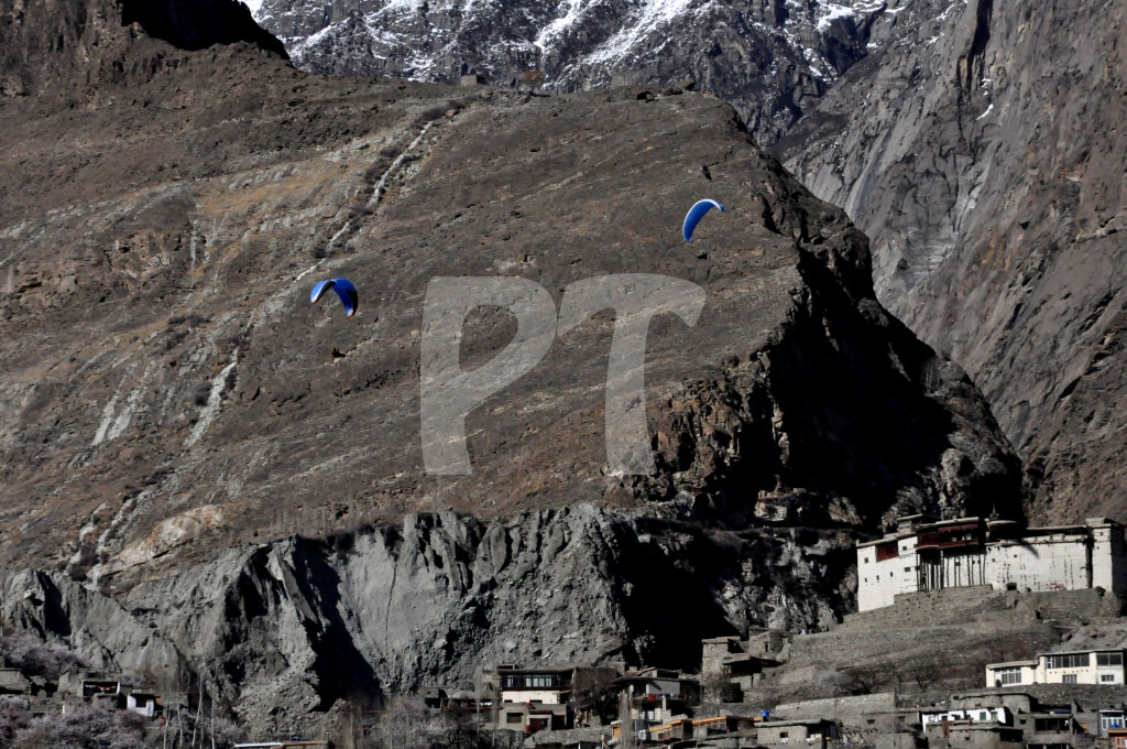 Two paragliders hover over the Baltit Town