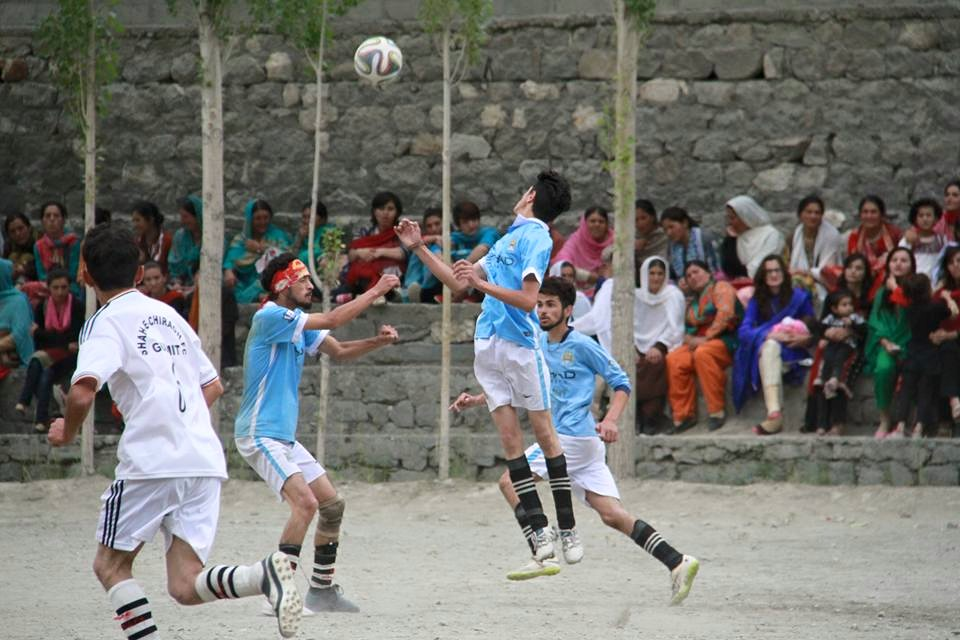 Players compete for the ball during the match as women sitting in the audience watch. Photo: Rehmat Jabbar